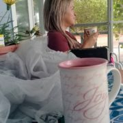 Vibrant Vanessa enjoying her morning coffee on the quaint cottage porch during Coach Training at the beach.